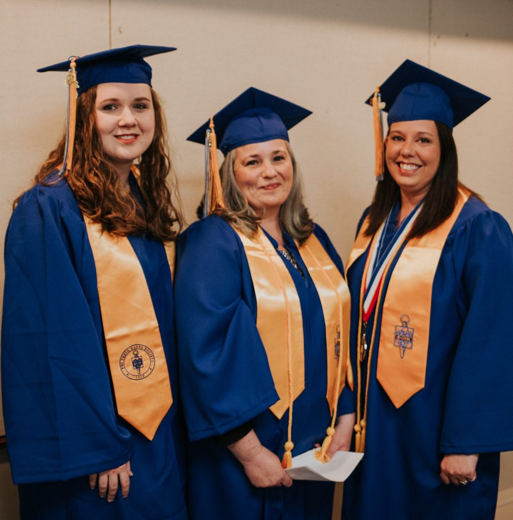 Three female students wearing caps and gowns