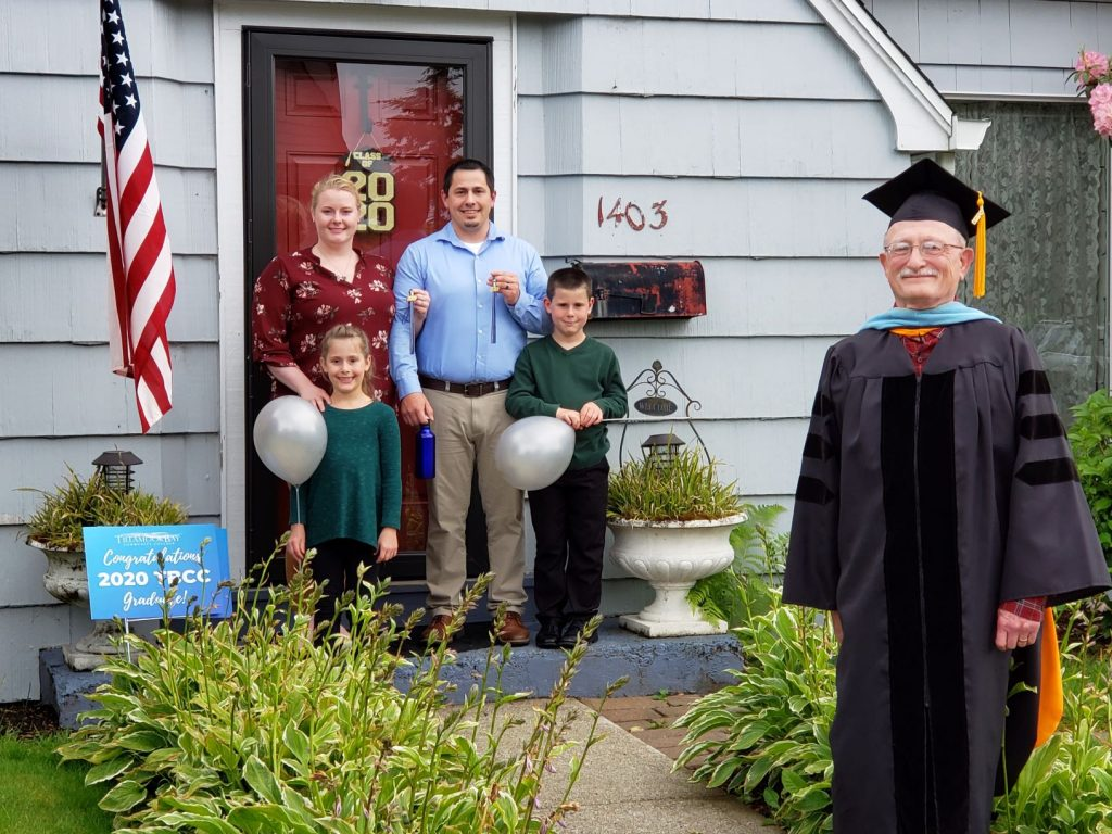 Photo of two graduates with their family