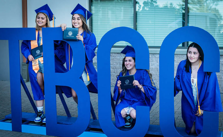 Graduates posing by letters TBCC 2021 Graduation